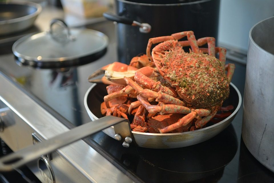 Cooking crabs in a pan on an induction stove