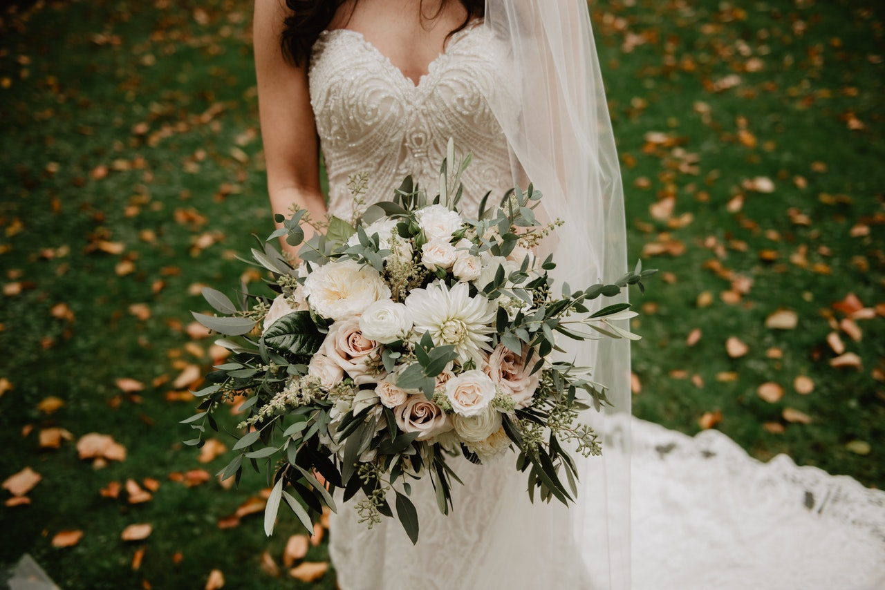 A bride in her white dress holding a bouquet of white flowers