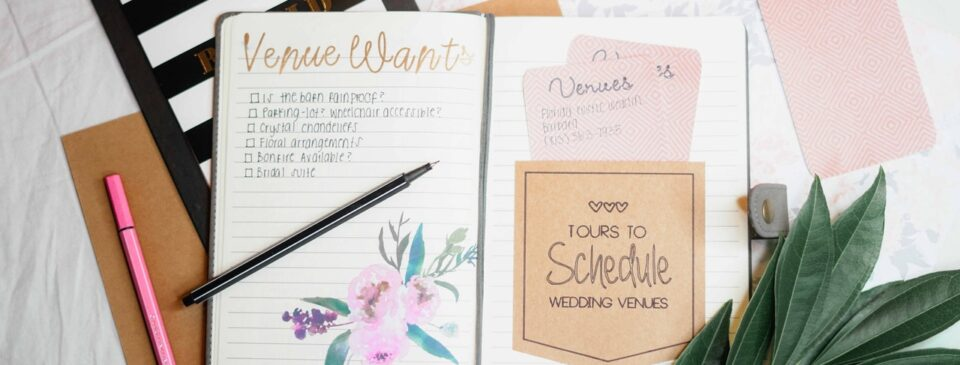 A pink pen placed next to a wedding planner placed on a table